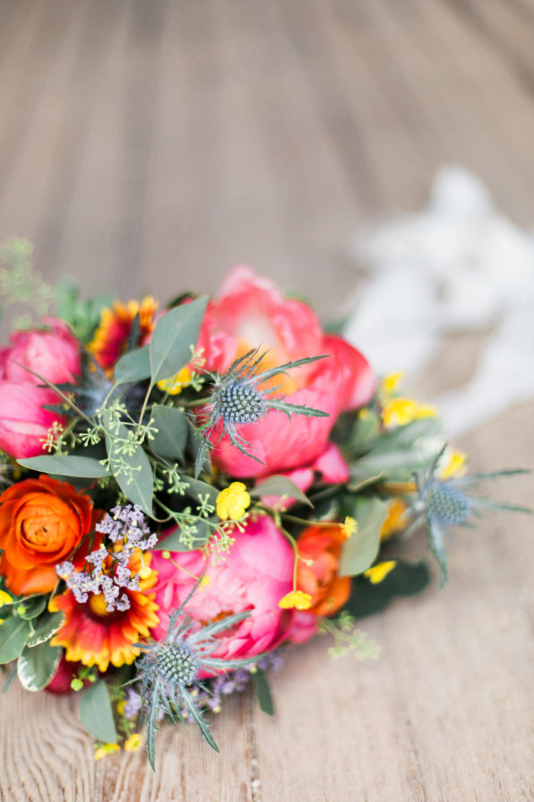Lovely sunset themed bridal bouquet. Featuring coral peonies, eucalyptus, blanket flowers, statice and globe thistle. Bouquet tied with delicate white, long ribbon.