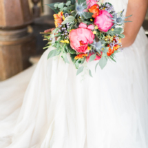 Lovely sunset themed bridal bouquet. Featuring coral peonies, eucalyptus, blanket flowers, statice and globe thistle. Bouquet tied with delicate white, long ribbon. Missoula Montana Flowers Delicate and Rustic Wedding
