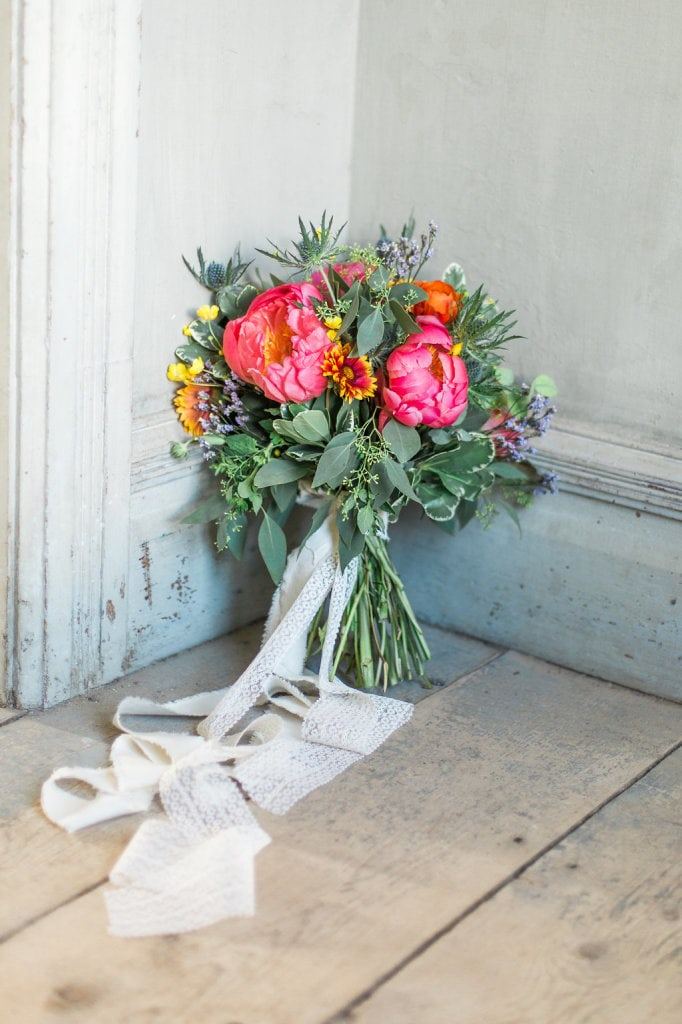 Lovely sunset themed bridal bouquet. Featuring coral peonies, eucalyptus, blanket flowers, statice and globe thistle. Bouquet tied with delicate white, long ribbon. Missoula Montana Flowers