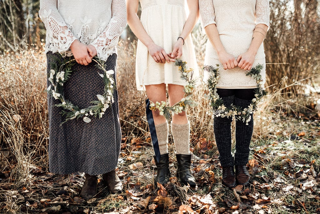 Three girls holding flower wreaths