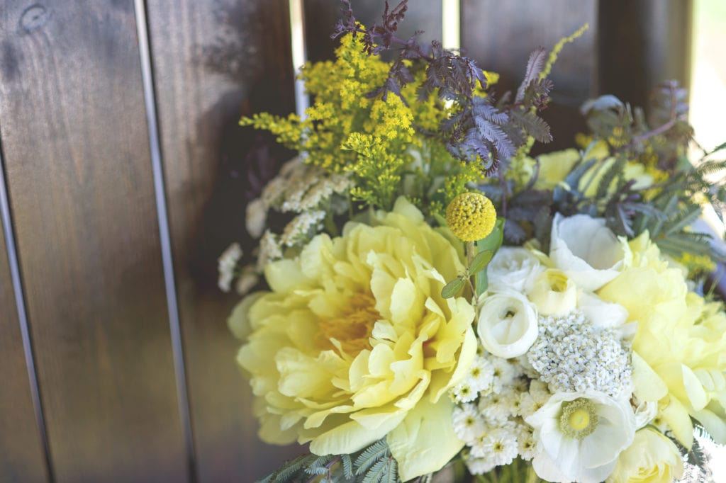 yellow yearrow, white anemone, white ranunculus and feverfew bridal bouquet for a montana wedding