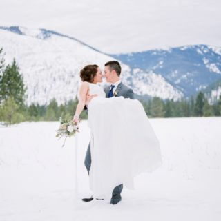 a lesbian couple with a Montana mountain background at a winter wedding
