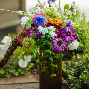 summer wildflower arrangement with pink and yellow zinnias, white sweet peas and bachelor buttons