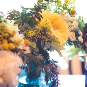 fresh flower arrangement with yellow and white peonies in a blue glass vase