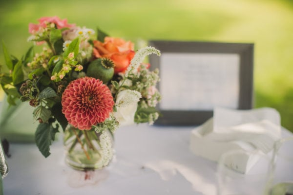 Seasonal small flower arrangement and vase with pink dahlias, white veronica, peach roses and raspberry leaf