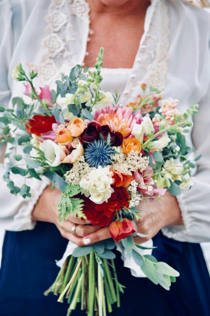 colorful bouquet of flowers held in both hands of woman in white shirt