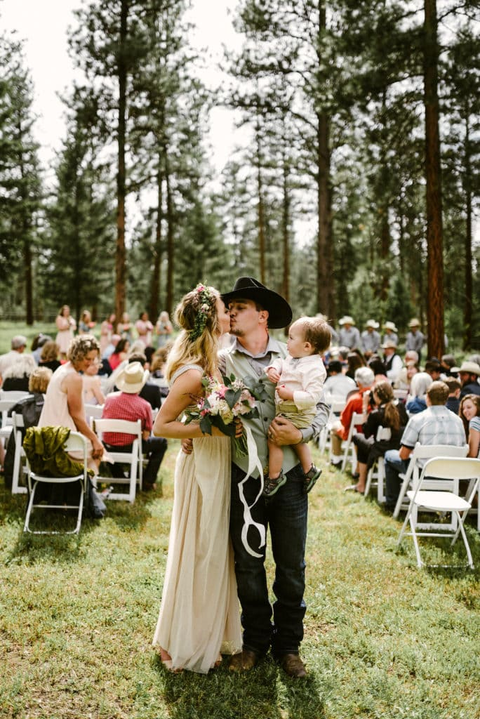 Man in a cowboy hat holding his son kissing his bride who is holding a beautiful pink and coral peony bouquet