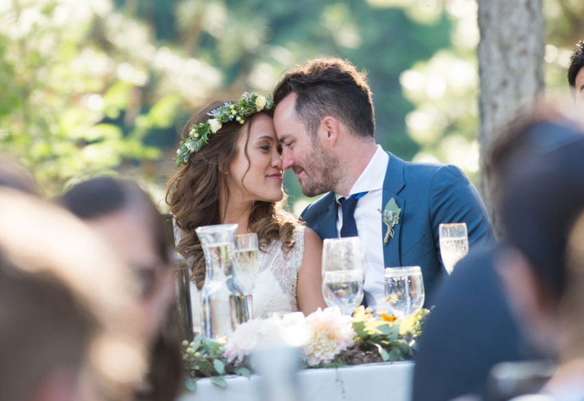 bride and groom with heads together at table