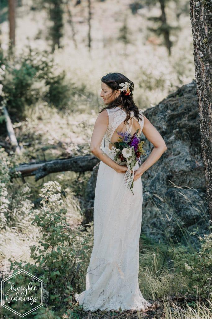 bride holding wildflower bouquet at white raven avenue