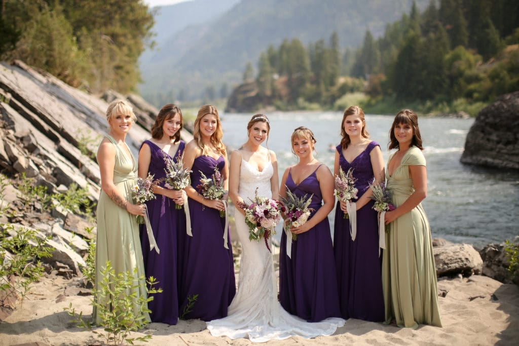bride with her bridesmaids holding their bouquets standing infront of the alberton gorge at white raven avenue in alberton, Montana