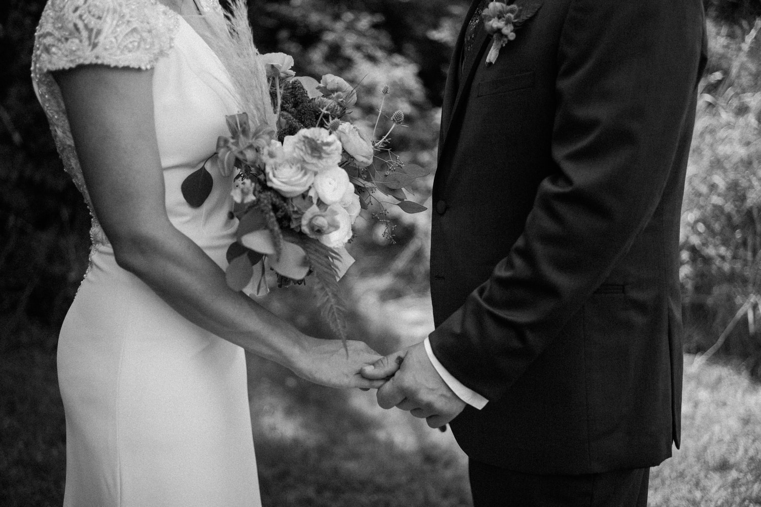 black and white closeup of bride and groom holding hands