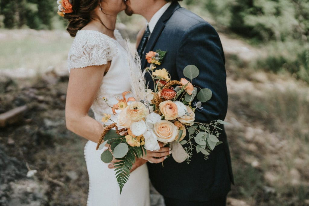 Bride holds bouquet while kissing groom