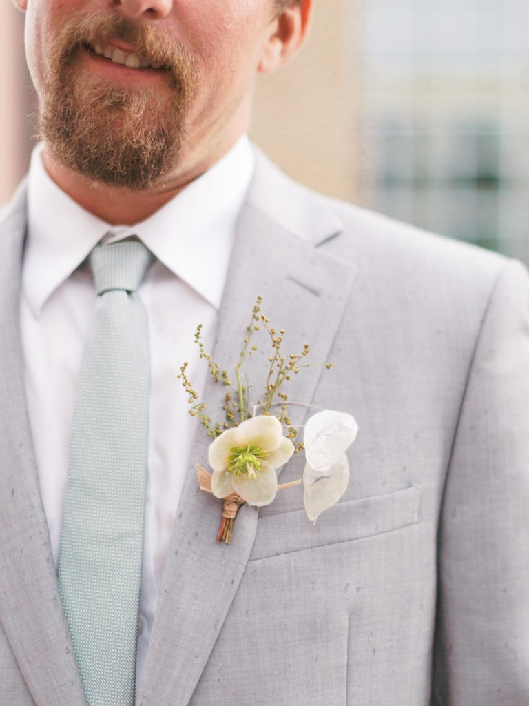 Groom wearing gray suit with boutonniere in Missoula wedding