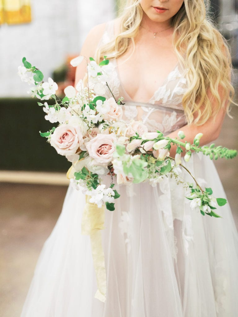 Bride holding bouquet of dried flowers, hellebore, and roses