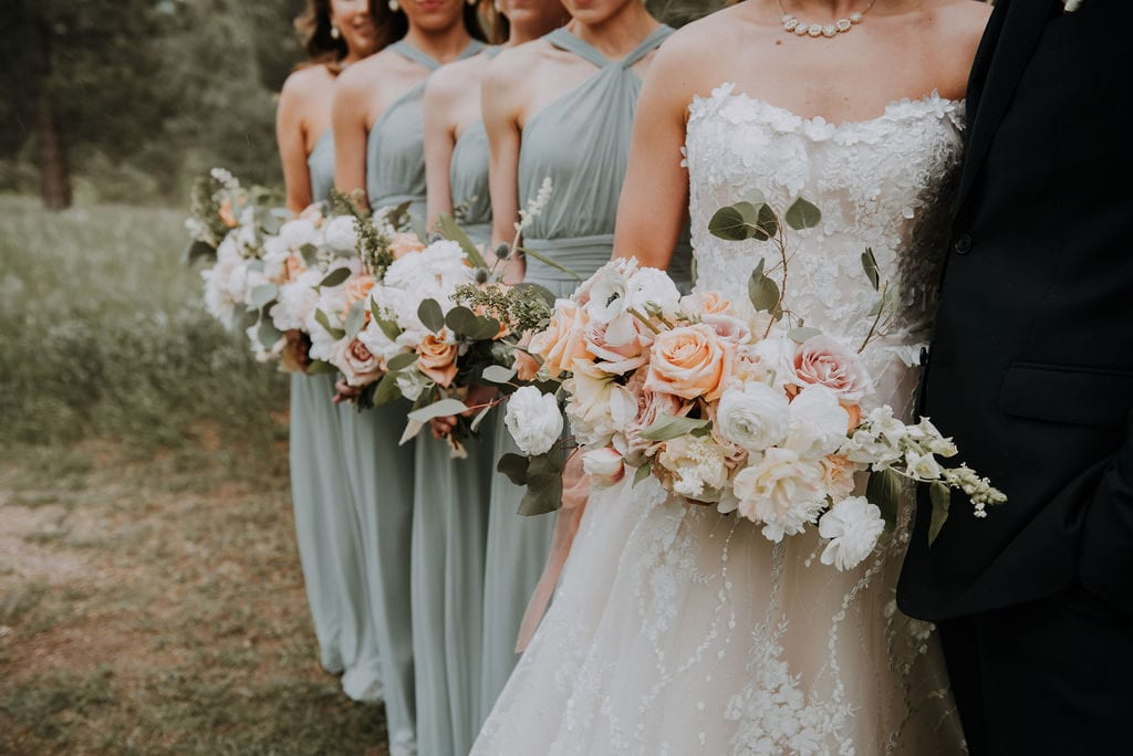 bride and bridesmaids lined up showing off bouquets