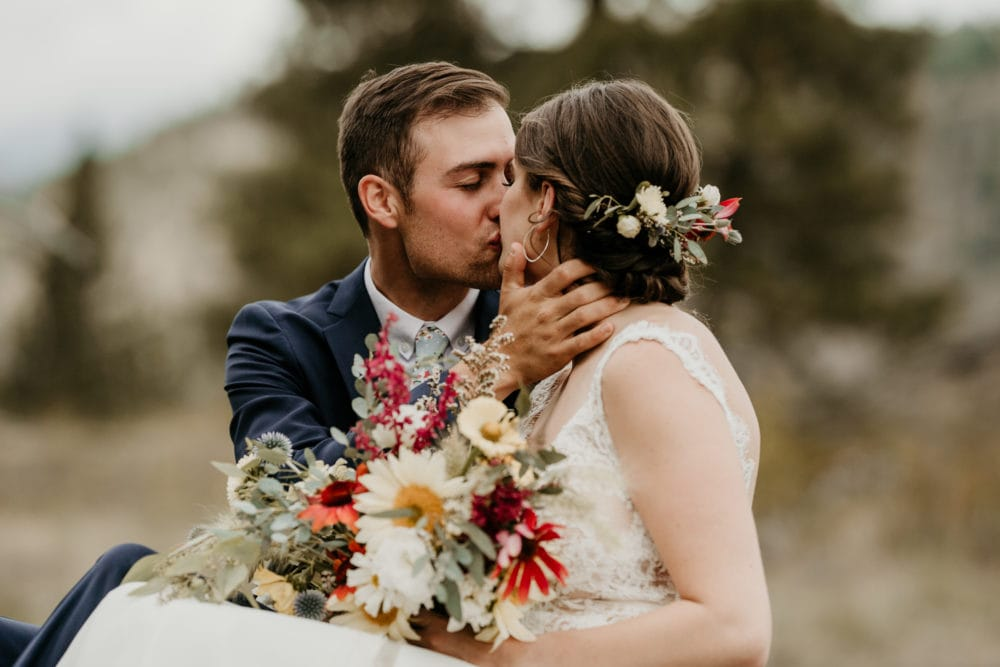 bride holding bouquet while kissing groom