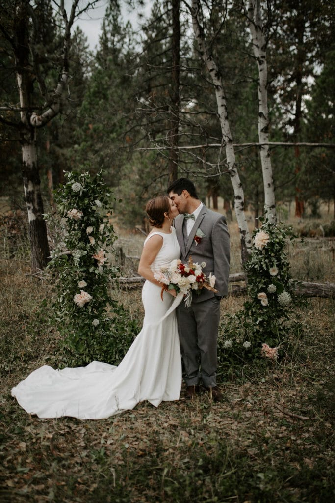 bride and groom kissing in front of arch