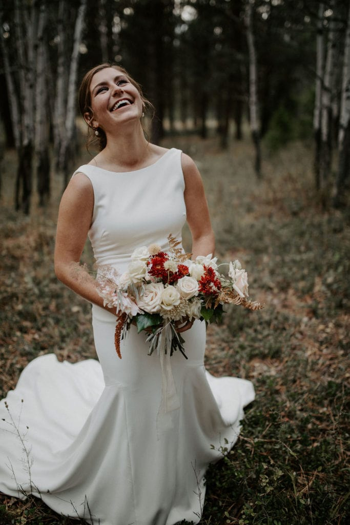 Bride laughing while holding bouquet