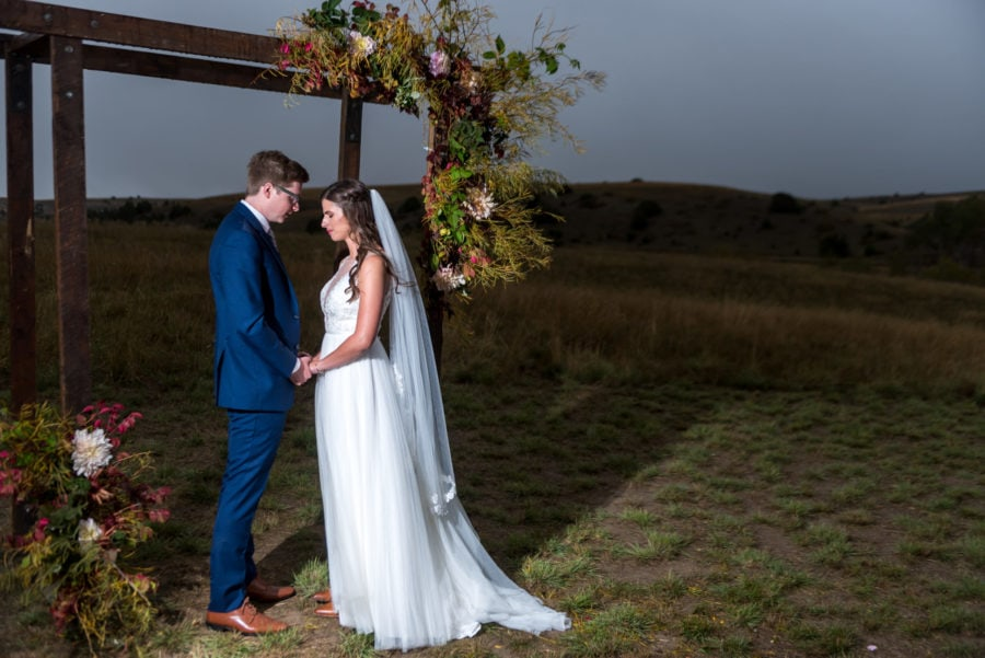 bride and groom standing under nature-inspired archway