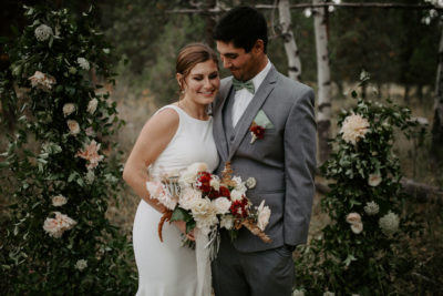 Bride and groom stand in front of floral installation arch